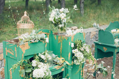 Beautifully decorated photo zona for wedding. Green chest of drawers decorated with white flowers. Beautifully decorated photo zona for a wedding. Green chest of Stock Image