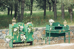 Beautifully decorated photo zona for wedding. Green chest of drawers decorated with white flowers. Beautifully decorated photo zona for a wedding. Green chest of Royalty Free Stock Photo