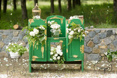Beautifully decorated photo zona for wedding. Green chest of drawers decorated with white flowers. Beautifully decorated photo zona for a wedding. Green chest of Stock Images