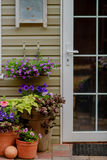 Beautifully decorated porch of a private house, colorful flowers in large clay pots, vintage bench, vintage inventory. Royalty Free Stock Image