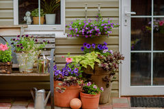 Beautifully decorated porch of a private house, colorful flowers in large clay pots, vintage bench, vintage inventory. Stock Photography