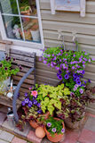 Beautifully decorated porch of a private house, colorful flowers in large clay pots, vintage bench, vintage inventory. Stock Photos