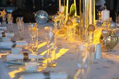Beautifully decorated table. With crystal candlesticks and candelabra at wedding reception, selective focus, table lighted a yellow beam Royalty Free Stock Photos
