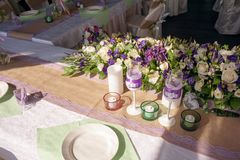 Beautifully decorated table for the wedding ceremony. Served banquet table decorated with fresh flowers in the open air Royalty Free Stock Photography