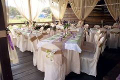 Beautifully decorated table for the wedding ceremony. Served banquet table decorated with fresh flowers in the open air Stock Image