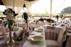Beautifully decorated table for the wedding ceremony. Served banquet table decorated with fresh flowers in the open air Royalty Free Stock Photo