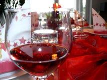 Beautifully dekorerad tabell med rött vinexponeringsglas i förgrunden Arkivfoton