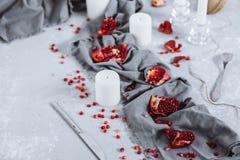 Beautifully dekorerad tabell med stycken av röd granatäpple, handdukar och stearinljus Matfoto med frukt royaltyfri fotografi