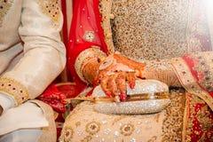 Beautifully dekorerade indiska brudhänder med brudgummen Royaltyfri Foto