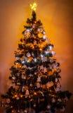 Beautifully dekorerade romantiker julgranen med mång- kulöra ljus på varm bakgrund Arkivbilder