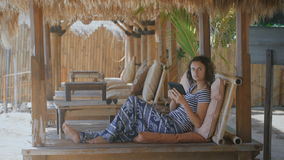 Beautifully dressed girl lying on a lounger on a tropical resort in Bali. Young woman uses tablet and smartphone while stock video footage