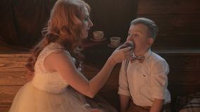 Beautifully dressed mother and son eating holiday cupcakes. Beautifully dressed young mother and her son eating holiday cupcakes stock video