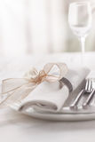 Beautifully elegant decorated table for holiday - wedding or valentine day with modern cutlery, bow, glass, candle and gift. Closeup, toned stock photo