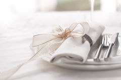 Beautifully elegant decorated table for holiday - wedding or valentine day with modern cutlery, bow, glass, candle and gift. Horizontal, closeup, toned stock photo