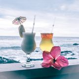 Beautifully garnished tropical cocktails on vacation, with sea i. Beautifully garnished tropical cocktails and a pink hibiscus flower on vacation, with sea in stock images
