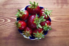 Beautifully laid out delicious large homemade red berry strawberries in a plate on a wooden table   close-up royalty free stock photo