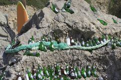 Beautifully laid out empty beer bottles on a huge boulder in a sunny weather. The beach of Tsampika, Rhodes island, Greece - September 21, 2017: Beautifully Stock Image