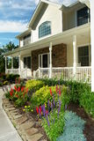 Beautifully landscaped home. Beautifully landscaped suburban home with colorful flowerbeds and porch on front of house Stock Photos