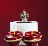 Beautifully lit lamps around Hindu Lord Ganesh Stock Photos