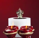 Beautifully lit lamps around Hindu Lord Ganesh Stock Photos