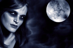 Beautifully mistic women in moonlight. Portrait of a beautifully dark mistic woman with moon in background Royalty Free Stock Image