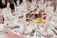 Beautifully organized event, glasses at served festive white table ready. Banquet, wedding decor. Cutlery and crockery Stock Photos