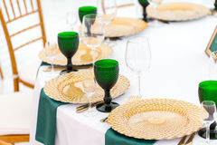 Beautifully organized event - served festive round tables ready for guests. Beautifully organized event - served festive tables ready for guests. gold plates and Royalty Free Stock Images
