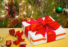 Beautifully packed gift by Christmas and the decorated fir-tree. Stock Photo