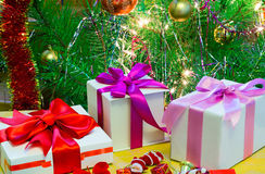 Beautifully packed gift by Christmas and the decorated fir-tree. Stock Photos