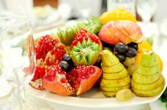 Beautifully served assorted fruits lie on a plate. Close-up royalty free stock photography