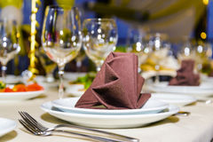 Beautifully served table in a restaurant. Beautiful table appointments for party in the restaurant, focus on napkin in center Royalty Free Stock Image