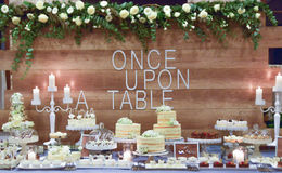 Beautifully served  table. Wedding or engamenent  reception.g wood wall wit text once upon  a table Stock Image