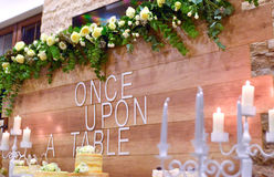 Beautifully served  table. Wedding or engamenent  reception.g wood wall wit text once upon  a table Stock Images