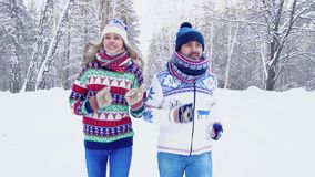 Beautifully-shot couple jogging in the winter forest. Slow motion stock video footage