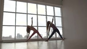 Beautifully-shot young women practicing extended triangle yoga pose together stock video footage