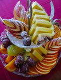 Beautifully sliced different fruits sprinkled with powdered sugar royalty free stock photography