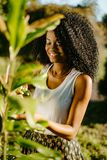 Beautifully smiling african girl with green eye shadows is taking care for outdoor plants by using the green plastic. Trigger spray royalty free stock image