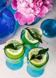Three refreshing tequila cocktails on a marble surface. Beautifully styled tequila cocktails in vintage blue glassware on a marble table stock image