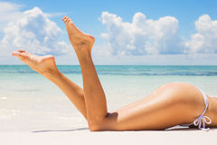 Beautifully tanned legs on the beach Stock Photo