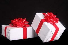 Beautifully wrapped Christmas present. S with  red bows isolated on a black background for a dramatic effect Stock Photo