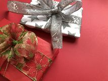 Two luxury wrapped Christmas gifts on a red background royalty free stock photos