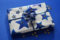 Beautifully wrapped gift decorated with a blue ribbon stock images
