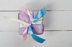 Beautifully wrapped gift in purple paper. On white wooden boards Stock Image