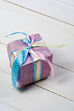 Beautifully wrapped gift in purple paper. On white wooden boards Royalty Free Stock Images