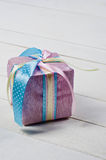 Beautifully wrapped gift in purple paper. On white wooden boards Stock Photos