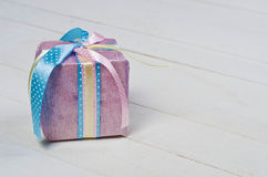 Beautifully wrapped gift in purple paper. On white wooden boards Stock Photography