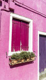 Beautifulpink building with pink windows and pot flowers in Burano island (Venice, Italy) Royalty Free Stock Photos