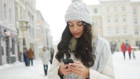 Beautifulwoman που φορούν το χειμερινό παλτό και χαμόγελο ευτυχές στέλνοντας το μήνυμα με το κινητό τηλέφωνο στην πόλη απόθεμα βίντεο