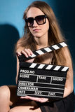 Beautifulwoman holding a movie clapper. Royalty Free Stock Photos