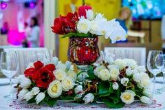 Beautifuly adornó la tabla de la recepción nupcial cubierta con las flores frescas Imagenes de archivo